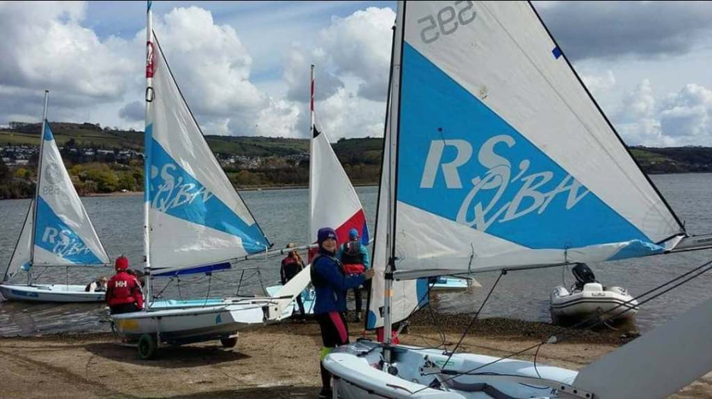 Students at Paignton sailing club, in full winter sailing gear, putting dinghies in the water. photo used with permission from Maria A Bown
