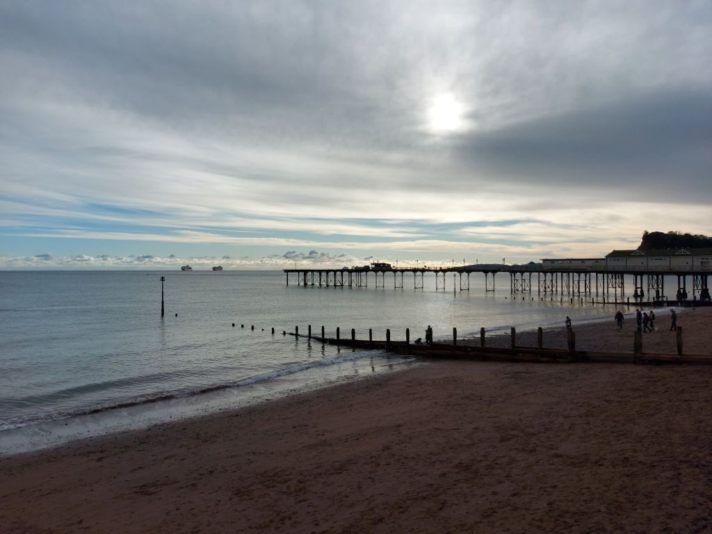 A view of Teignmouth pier with two cruise ships at anchor on the horizon