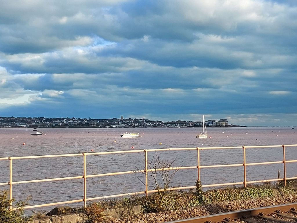 A view of Exmouth from across the estuary and trainline, a yacht and other boats can be seen at their moorings.
