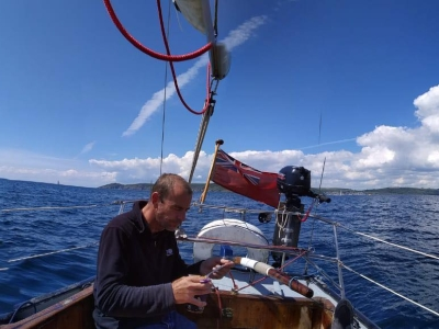 Justin, alone at the helm of a wooden yacht, a lot of open water is visible and only a small amount of land can be seen on the horizon is